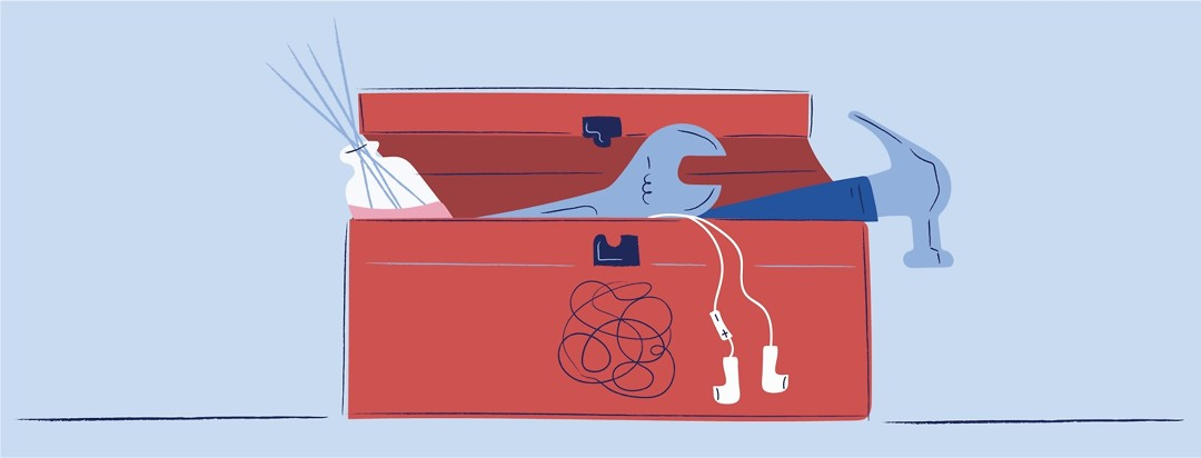 A toolbox with a hammer, wrench, reed diffuser, and headphones sticking out
