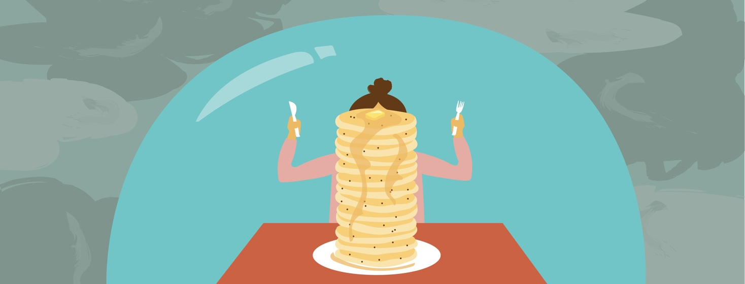 woman about to eat a large stack of pancakes