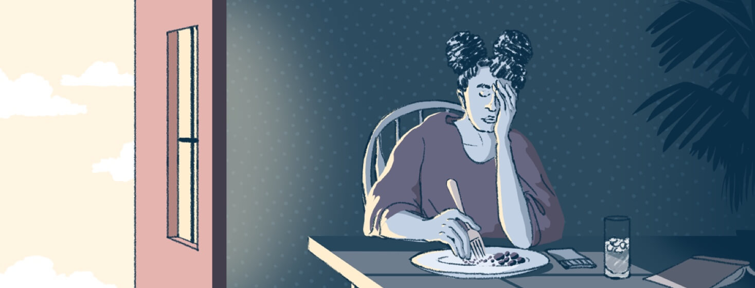 woman sitting at a table in the dark looking very tired and fatigued