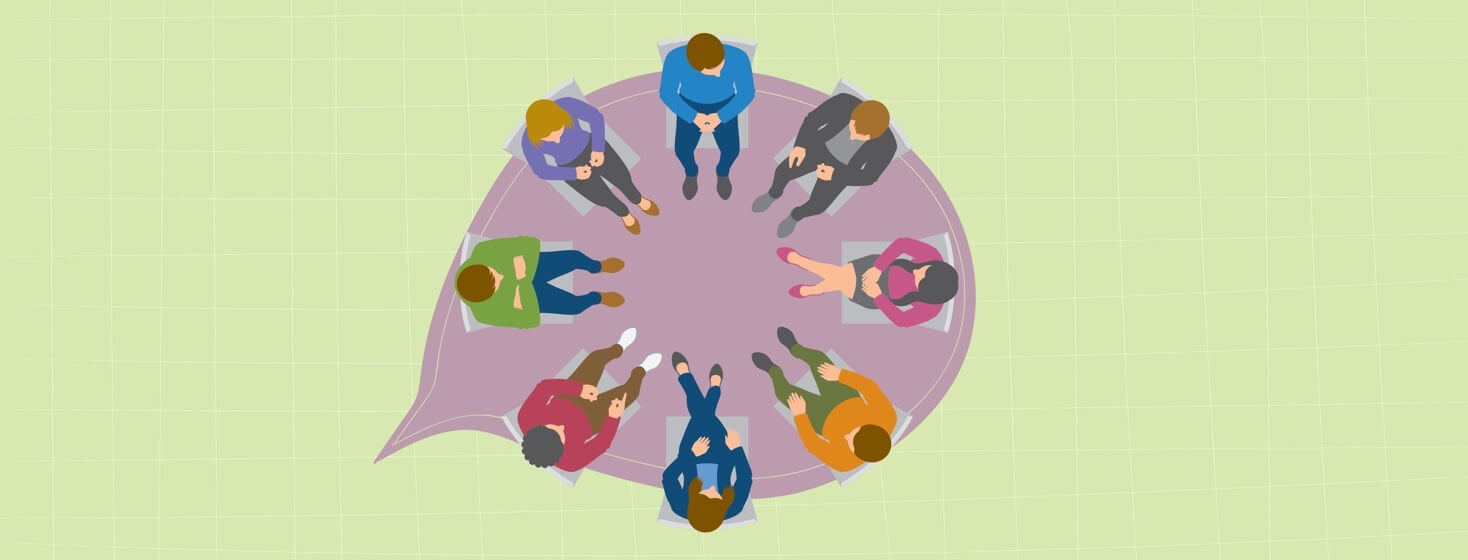 group of people sitting in a circle talking