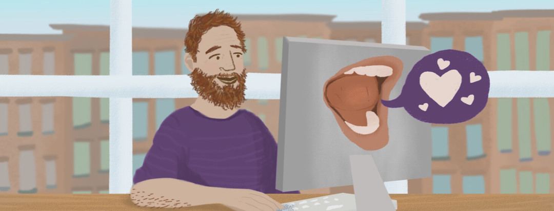 Man using a computer that has a mouth on it with a speech bubble filled with hearts