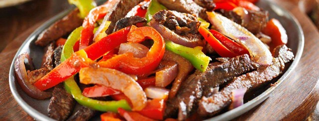 Plate of stir fried steak, bell peppers, and onions.