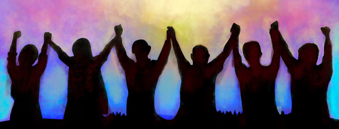 A group of silhouetted people raise their arms together facing a sunset