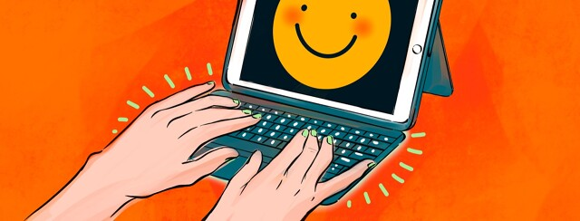 Hands typing at an ipad with a smiling face on screen