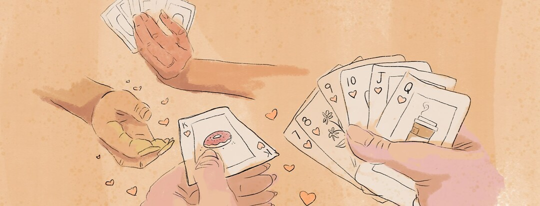 Two people playing cards; one person is handing the other person a playing card with a donut on it