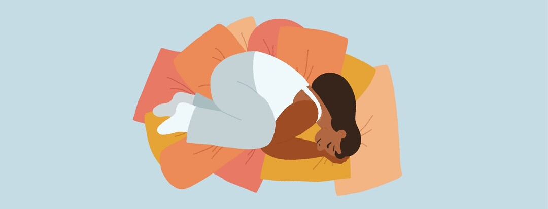 A woman curled up in a pile of pillows